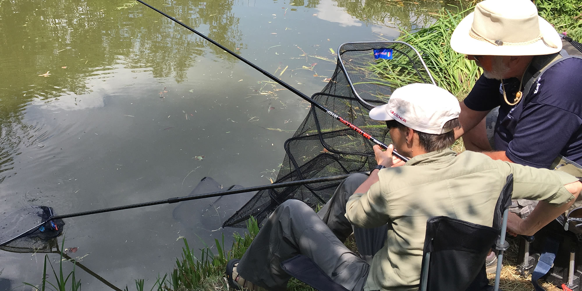 Male and coach coarse fishing at a Get Fishing beginner angling event